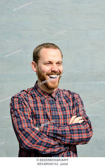 Portrait of laughing young man wearing checkered shirt