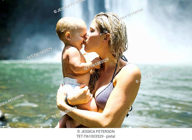 Mother kissing baby (18-23 months) with love