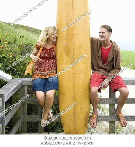 Mature couple sitting on a wooden fence with a surfboard