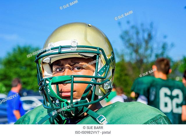 Portrait teenage male American football player wearing helmet at playing field