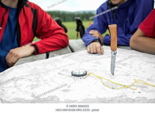 hikers determining their destination with random knife throw