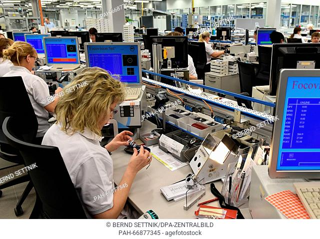 Opticians controlling the quality of glasses before shipping at Rathenower Optik GmbH in Rathenow, Germany, 8march 2016