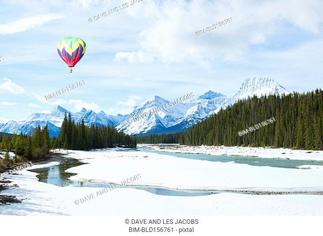 Hot air balloon floating over snowy river and mountains, Banff, Alberta, Canada