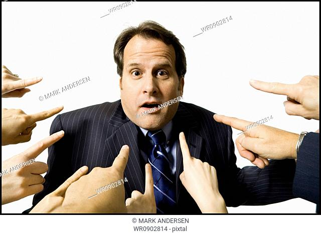 Businessman with fingers pointing at him