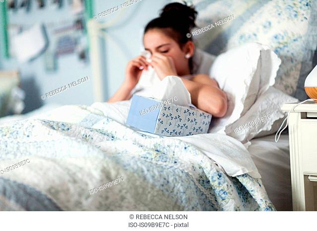 Girl in bed blowing nose on handkerchief