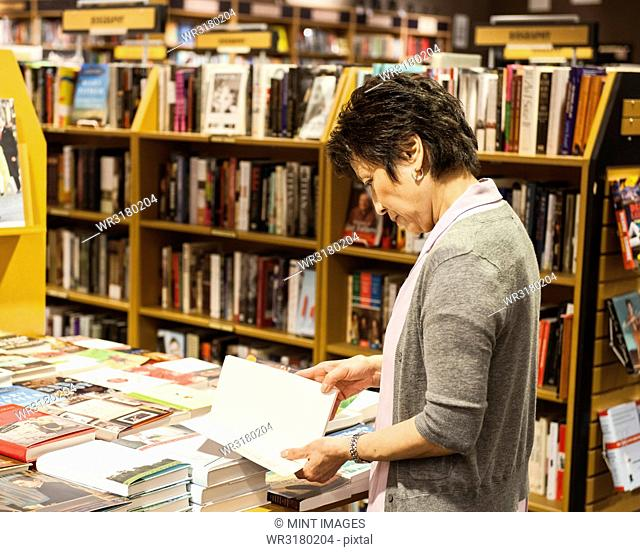 Asian American female browsing through books in a bookstore
