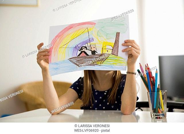 Little girl hiding behind her drawing