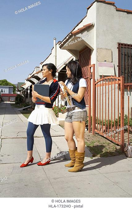 Side profile of two college students standing on the street