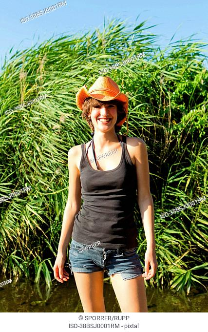 Woman in cowboy hat smiling outdoors