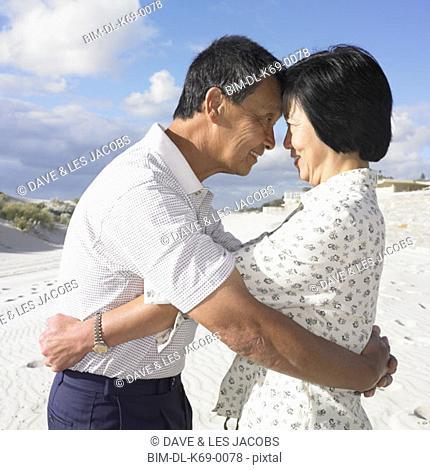 Senior Asian couple hugging at the beach, Perth, Australia