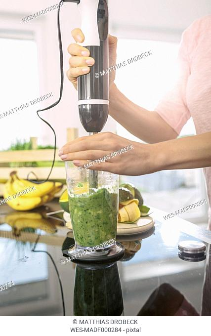 Smiling young woman preparing smoothie in the kitchen, close-up