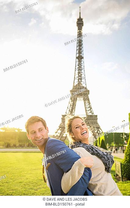 Caucasian couple playing near Eiffel Tower, Paris, France