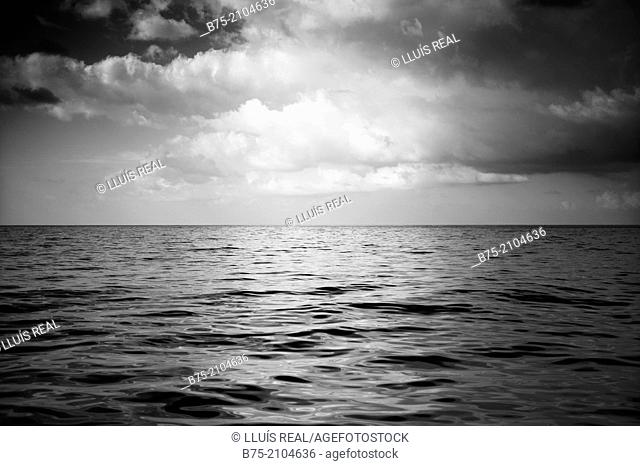 Calm sea landscape with clouds in the sky in black and white. Mediterranean sea, Balearic islands, Spain