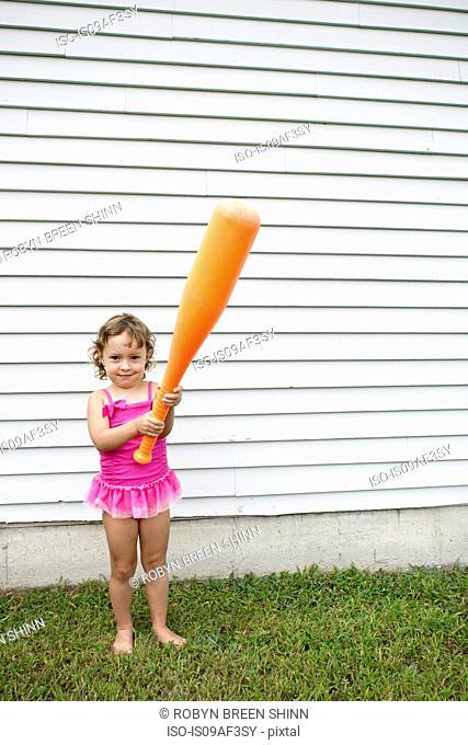 Female toddler in garden holding a large orange baseball bat