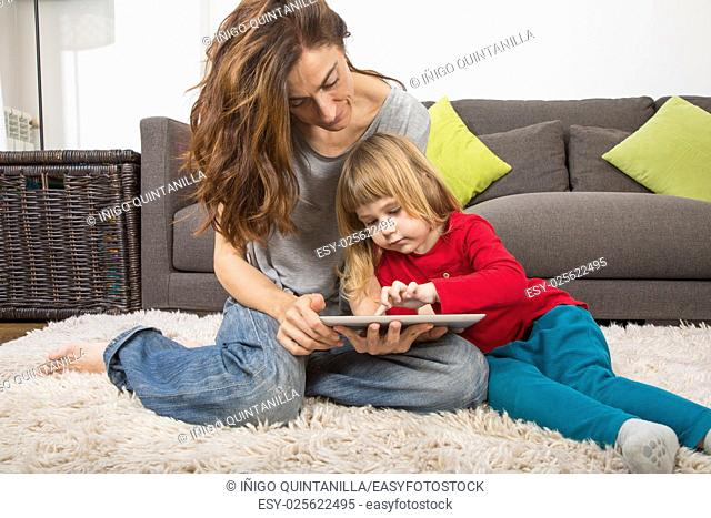 blonde three years old child and mother, with red, green and grey clothes, touching and watching digital tablet to surf internet, sitting on carpet indoor home