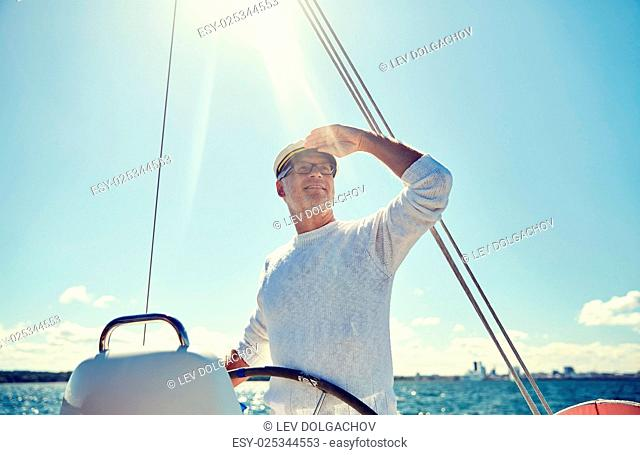 sailing, age, tourism, travel and people concept - happy senior man in captain hat on steering wheel and looking far away sail boat or yacht floating in sea