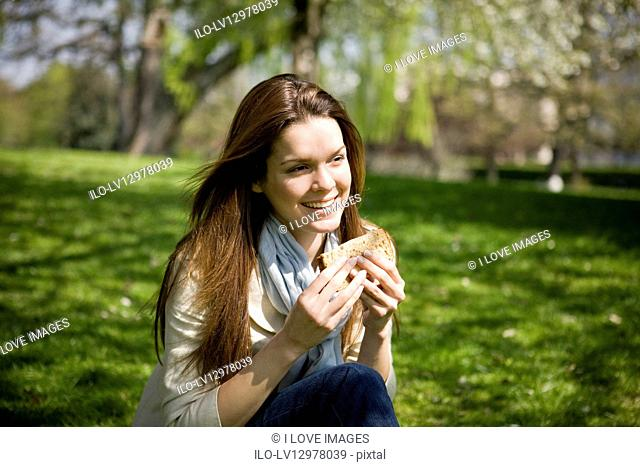 A young woman eating a sandwich, outdoors