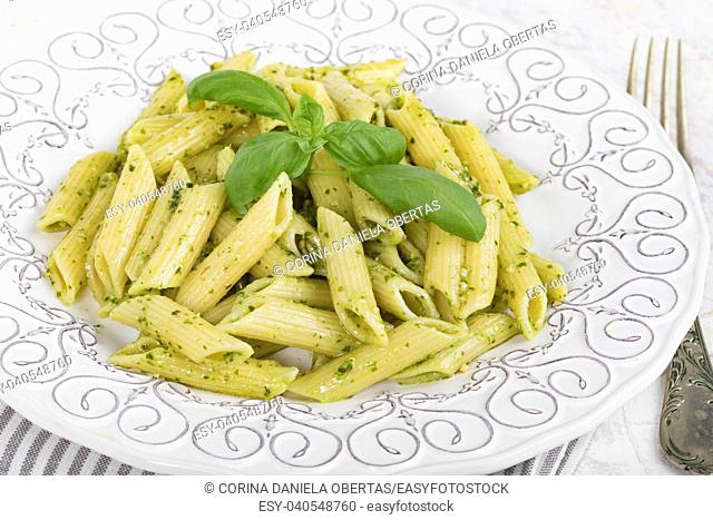 Closeup of plate with penne rigate pasta with basil pesto