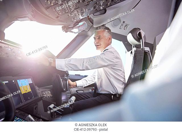 Smiling male pilot in airplane cockpit