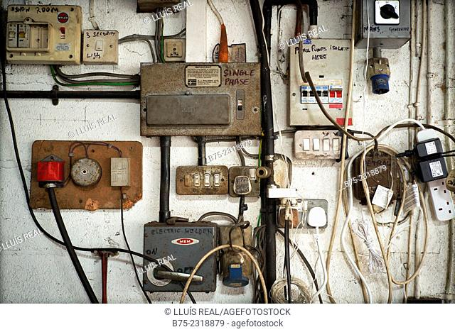 Electrical panel in a car garage with different switches, plugs, indications and electric cables. In Kettlewell, Skipton, Yorkshire Dales, England, UK, Europe