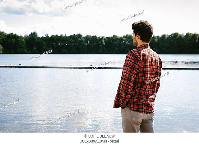 Young man looking across water