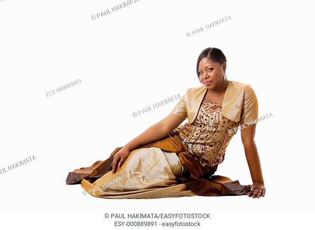 Beautiful African American woman in brown with gold dress, sitting laying on floor, isolated