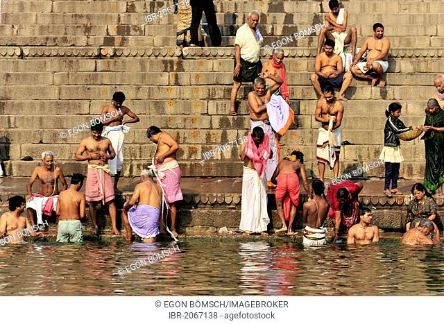 Believers performing ritual purifications on the banks of the Ganges River in Varanasi, Benares, Uttar Pradesh, India, South Asia