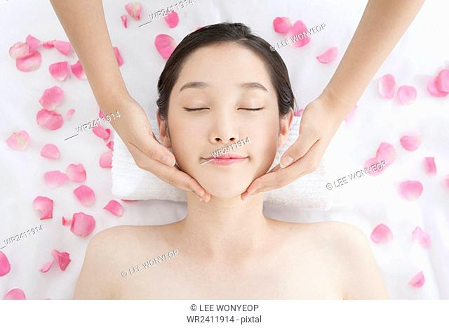 Portrait of young woman getting a massage closing her eyes