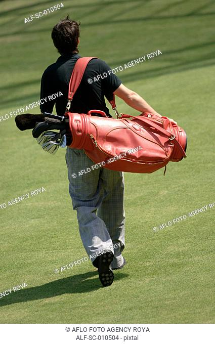 Rear view of a man carrying a red golf bag