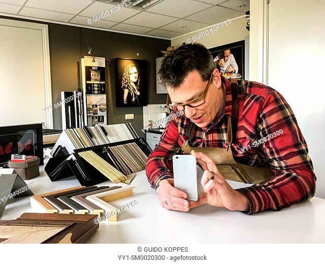 Goirle, Netherlands. Craftsman making a mobile photo with his iPhone smartphone