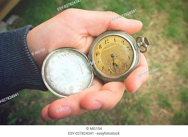Old pocket watch in a man's hand