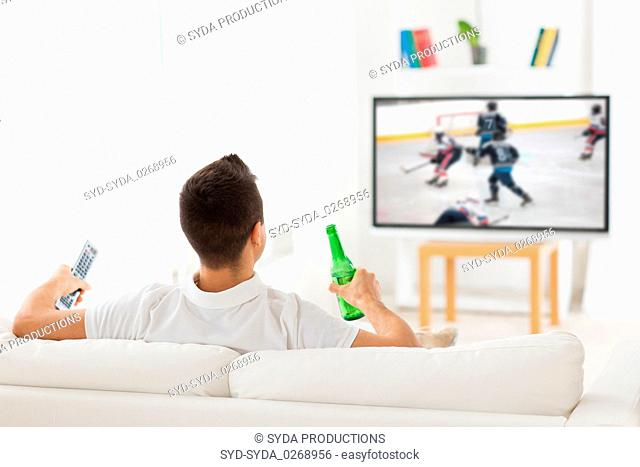 man watching ice hockey on tv and drinking beer