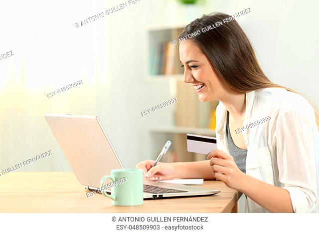 Side view portrait of a consumer paying on line at home