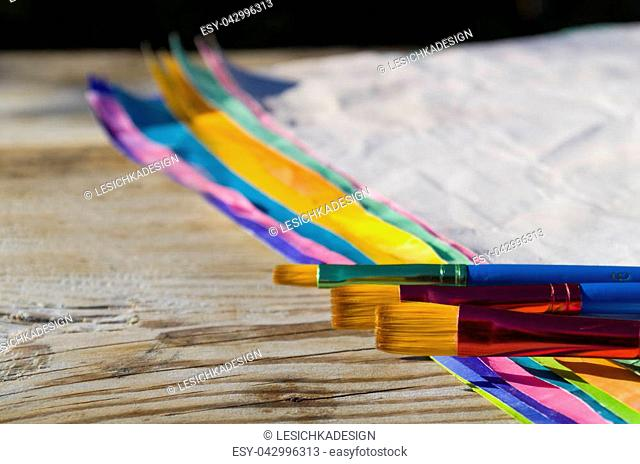 Paint brushes and colored paper on wooden background. Art background. Art supplies