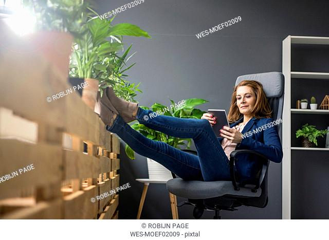 Mature businesswoman working in sustainable office, using digital tablet