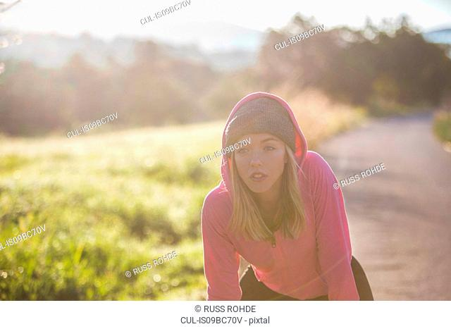 Young woman outdoors, taking a break from exercising