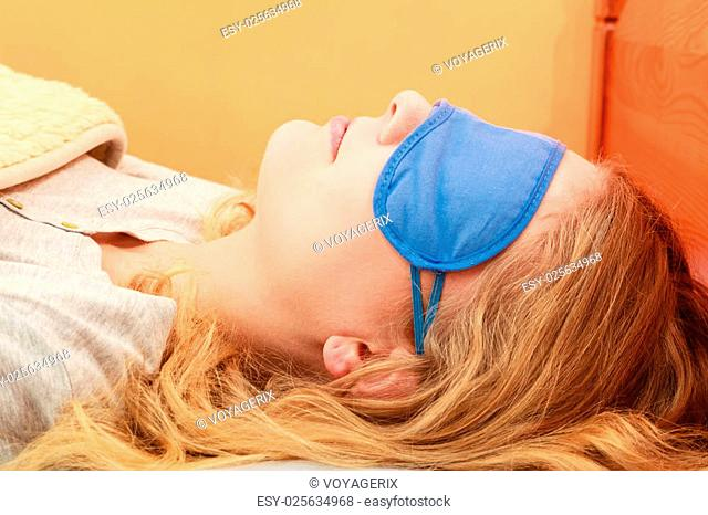 b267b128c88 Tired woman sleeping in bed wearing blindfold sleep mask. Young girl taking  nap