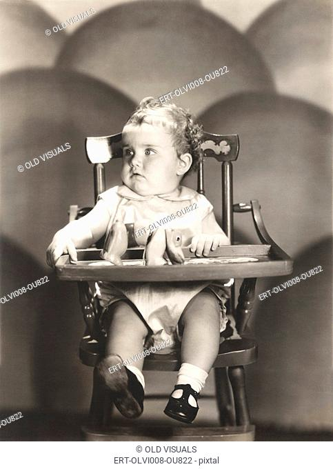 Cute baby sitting on high chair