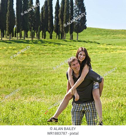 Italy, Tuscany, Man giving piggy back ride to woman on meadow