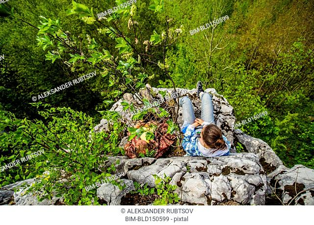 High angle view of Caucasian girl sitting on cliff edge