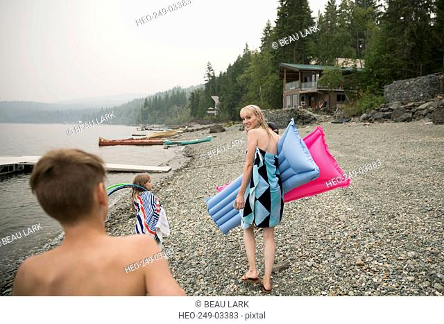 Family carrying pool rafts on lakeside beach