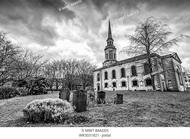 Exterior view of St Paul's Church and tombstones in churchyard under a cloudy sky, black and white image