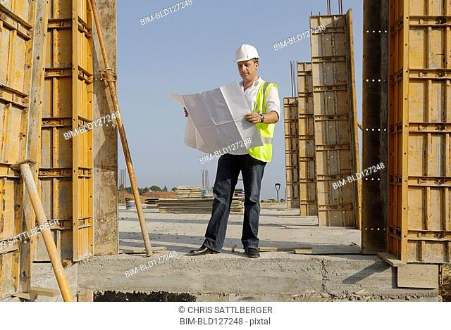 Male engineer wearing hard hat looking at plans on building site