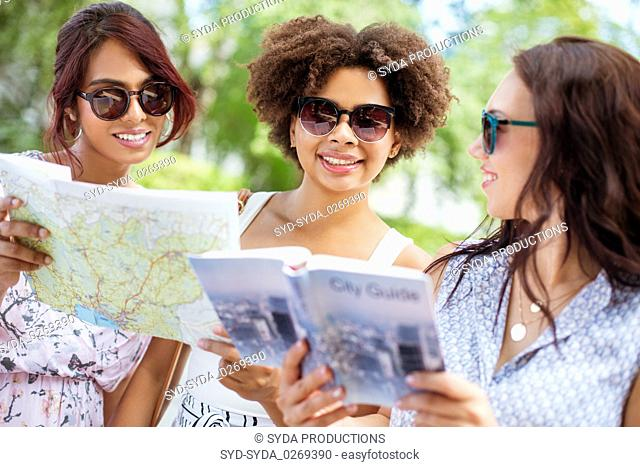 women with map and city guide on street in summer