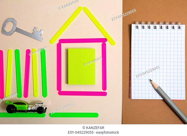 House of counting sticks car key to the apartment and a notebook with a pencil. Dream project of your house