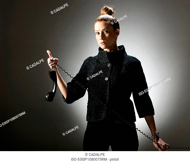 Businesswoman holding telephone by cord