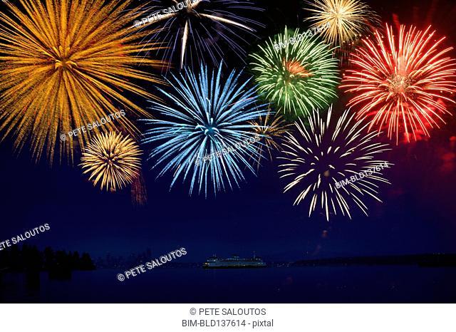 Fireworks exploding over cruise ship in bay, Seattle, Washington, United States