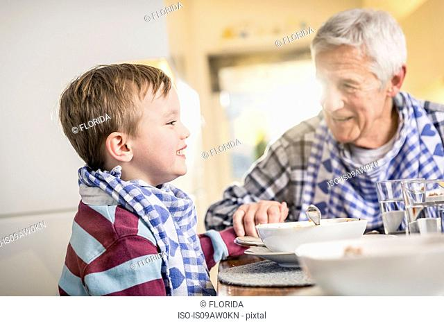 Senior man and grandson holding hands at lunch table