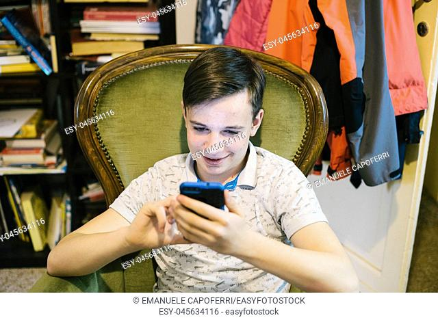teen boy looks at the smartphone in his home- portrait of boy reading on the smartphone