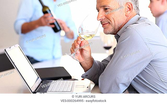 A senior businessman drinking a glass of white wine while at work